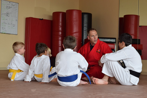 David Younglove in a huddle with his students at USA Karate in Rosemount, Minnesota