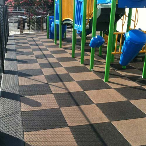 Playground flooring rubber tiles installation at a park.